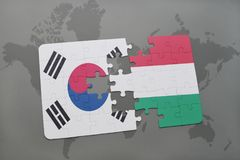 Puzzle with the national flag of south korea and hungary on a world map background. 3D illustration stock photography