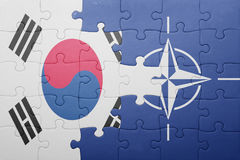 Puzzle with the national flag of south korea and nato. Concept royalty free stock photo
