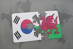Puzzle with the national flag of south korea and wales on a world map background. 3D illustration stock photos