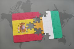 Puzzle with the national flag of spain and cote divoire on a world map background. 3D illustration Stock Photos