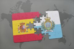 Puzzle with the national flag of spain and san marino on a world map background. Royalty Free Stock Photos