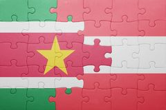 Puzzle with the national flag of suriname and austria. Concept Royalty Free Stock Photos