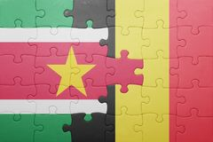 Puzzle with the national flag of suriname and belgium. Concept Royalty Free Stock Photography