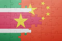 Puzzle with the national flag of suriname and china. Concept Stock Image