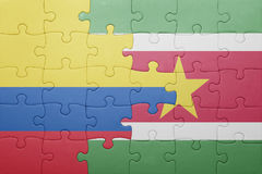 Puzzle with the national flag of suriname and colombia Royalty Free Stock Image