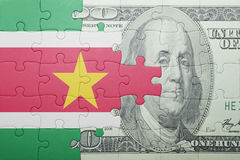 Puzzle with the national flag of suriname and dollar banknote Stock Images