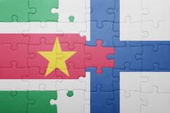 Puzzle with the national flag of suriname and finland Royalty Free Stock Images