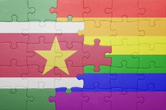Puzzle with the national flag of suriname and gay flag. Concept Stock Images