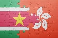 Puzzle with the national flag of suriname and hong kong. Concept Stock Image