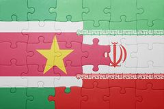 Puzzle with the national flag of suriname and iran. Concept Royalty Free Stock Image