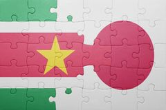 Puzzle with the national flag of suriname and japan. Concept Royalty Free Stock Image