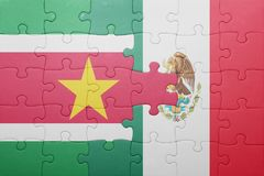Puzzle with the national flag of suriname and mexico. Concept stock photography
