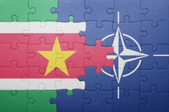 Puzzle with the national flag of suriname and nato. Concept stock photo