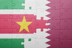 Puzzle with the national flag of suriname and qatar. Concept Royalty Free Stock Photography