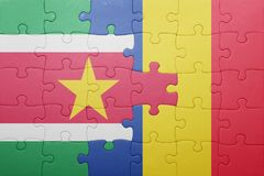 Puzzle with the national flag of suriname and romania. Concept Stock Images