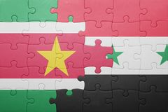Puzzle with the national flag of suriname and syria. Concept Stock Image