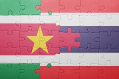 Puzzle with the national flag of suriname and thailand. Concept Stock Image