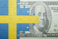 Puzzle with the national flag of sweden and dollar banknote. Concept Stock Photo