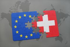 Puzzle with the national flag of switzerland and european union on a world map background. stock photo