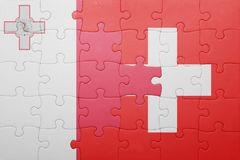 Puzzle with the national flag of switzerland and malta. Concept Royalty Free Stock Image