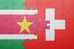 Puzzle with the national flag of switzerland and suriname. Concept Royalty Free Stock Image
