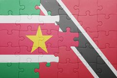 Puzzle with the national flag of trinidad and tobago and suriname Stock Images