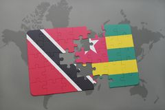 Puzzle with the national flag of trinidad and tobago and togo on a world map Stock Images