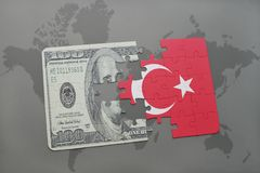 Puzzle with the national flag of turkey and dollar banknote on a world map background. Royalty Free Stock Photos