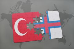 Puzzle with the national flag of turkey and faroe islands on a world map background. 3D illustration royalty free stock images