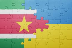 Puzzle with the national flag of ukraine and suriname. Concept Stock Photo