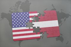 Puzzle with the national flag of united states of america and latvia on a world map background. Concept Stock Photo