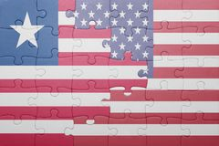 Puzzle with the national flag of united states of america and liberia. Concept royalty free stock photography
