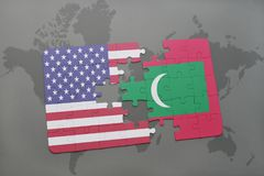 Puzzle with the national flag of united states of america and maldives on a world map background. Concept Stock Photos