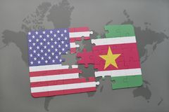 Puzzle with the national flag of united states of america and suriname on a world map background. Concept Stock Image