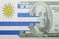 Puzzle with the national flag of uruguay and dollar banknote Stock Image