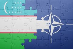 Puzzle with the national flag of uzbekistan and nato Royalty Free Stock Image