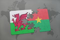 Puzzle with the national flag of wales and burkina faso on a world map Royalty Free Stock Photo