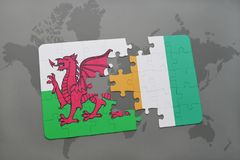 Puzzle with the national flag of wales and cote divoire on a world map. Background. 3D illustration Royalty Free Stock Photography