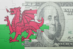 Puzzle with the national flag of wales and dollar banknote. Concept stock illustration