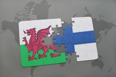 Puzzle with the national flag of wales and finland on a world map background. Royalty Free Stock Images