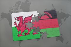 Puzzle with the national flag of wales and malawi on a world map Stock Photography