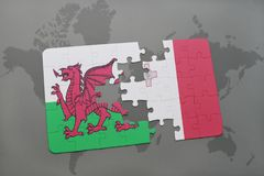 Puzzle with the national flag of wales and malta on a world map background. Stock Photo