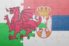 Puzzle with the national flag of wales and serbia . concept Stock Photos