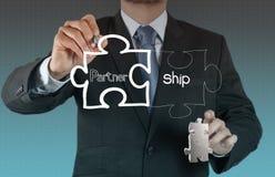 Puzzle partnership. Businessman hand shows light and puzzle partnership Royalty Free Stock Photo