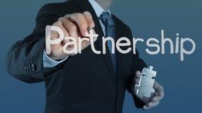 Puzzle partnership. Businessman hand shows light and puzzle partnership Royalty Free Stock Photos