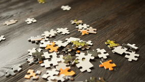 Puzzle parts falling on dark table stock footage