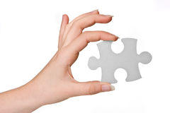 Puzzle piece. Hands of a woman holding a puzzle piece Stock Photos