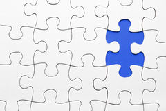 Puzzle piece in blue. Many pieces of the puzzle in white and one puzzle piece in blue royalty free stock photography