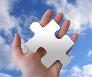 Puzzle Piece in Hand. A hand is holding a puzzle piece against a cloudy sky Stock Image