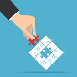 Puzzle piece in hand. Puzzle with assembled white and missing red piece in hand on blue background. Teamwork, partnership and solution concept. Flat design Stock Photography